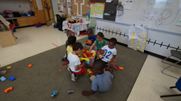 Kindergarten students playing in a classroom.
