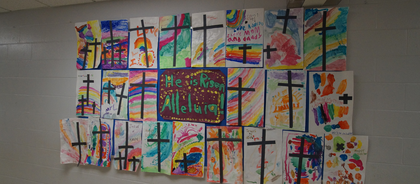 "Decorative paintings with crosses and rainbow colours with ""He is Risen, Alleluia!"" painted in the middle."