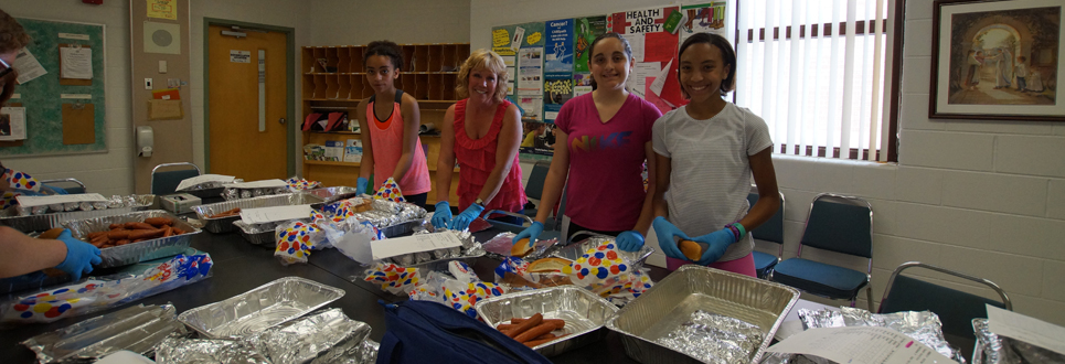 Volunteer with three students during hot dog day.