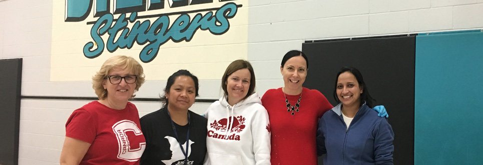 Five female adults standing in a school gym volunteering